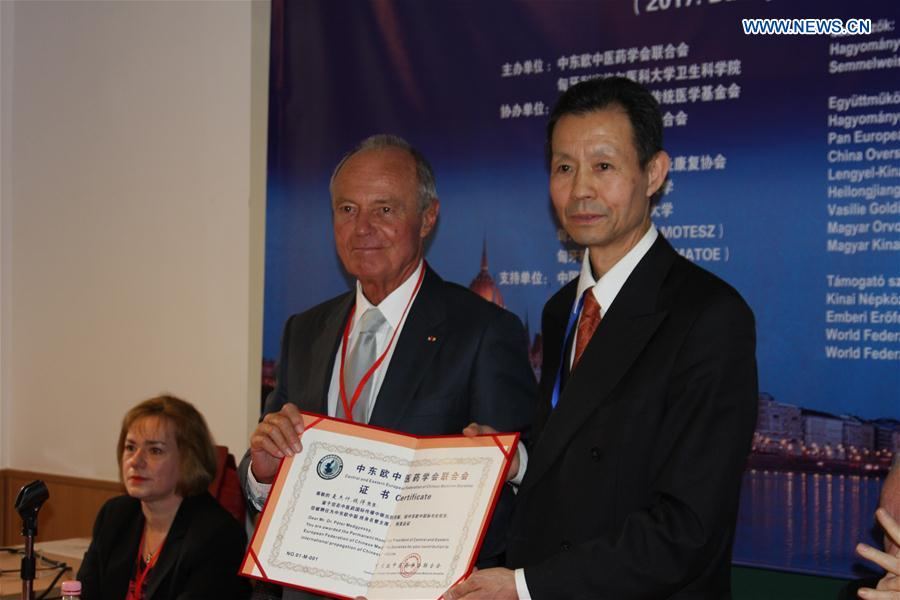 President of the Central and Eastern European Federation of Chinese Medicine Societies Yu Funian (R) presents the letter of appointment as Permanent Honorary President of the federation to former Hungarian Prime Minister Peter Medgyessy at the founding ceremony in Budapest, Hungary, March 4, 2017.