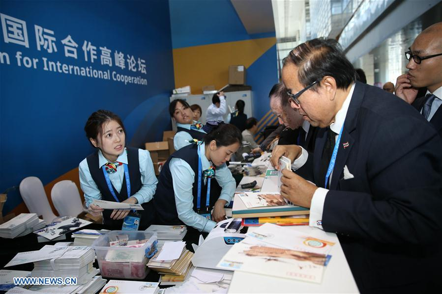 Staff members sell commemorative first-day covers featuring the Belt and Road Forum (BRF) for International Cooperation at the China National Convention Center in Beijing, capital of China, May 14, 2017.The Belt and Road Forum (BRF) for International Cooperation opened in Beijing on Sunday. (Xinhua/Cai Yang)<br/>