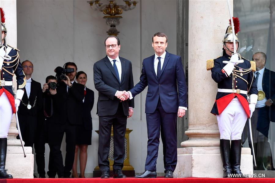 French president Emmanuel Macron (Front R) shakes hands with the outgoing French president Francois Hollande (Front L) during an inauguration ceremony at the Elysee Palace in Paris, France, on May 14, 2017. Centrist Emmanuel Macron was sworn in as the eighth president of the French Fifth Republic in a ceremony at the Elysee Palace here on Sunday. (Xinhua/Chen Yichen)<br/>