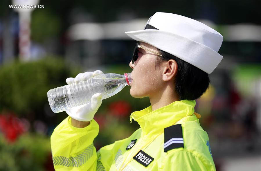 A traffic policewoman drinks water while on duty in Hengshui City, north China's Hebei Province, July 12. In the persistent heat of this summer, workers of many occupations kept working on their posts. (Xinhua/Zhu Xudong)<br/>