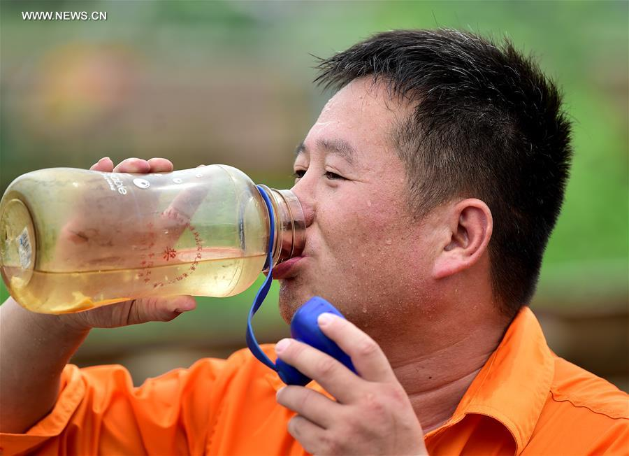 A railway worker drinks water during a break of work in Hefei City, capital of east China's Anhui Province, July 12, 2017. In the persistent heat of this summer, workers of many occupations kept working on their posts. (Xinhua/Liu Junxi)<br/>