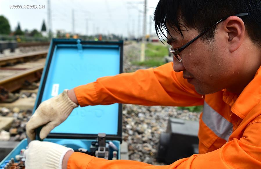 A railway worker checks the running status of equipment in Hefei City, capital of east China's Anhui Province, July 12, 2017. In the persistent heat of this summer, workers of many occupations kept working on their posts. (Xinhua/Liu Junxi)<br/>