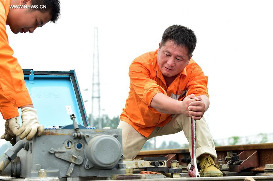 Two railway workers check the running status of equipment in Hefei City, capital of east China's Anhui Province, July 12, 2017. In the persistent heat of this summer, workers of many occupations kept working on their posts. (Xinhua/Liu Junxi)