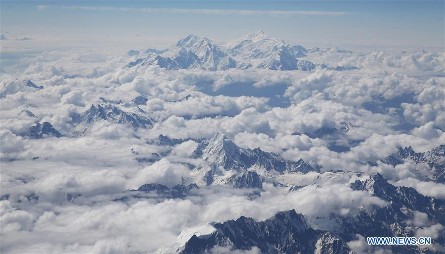 Aerial view of snow mountains in sea of clouds in China's Tibet