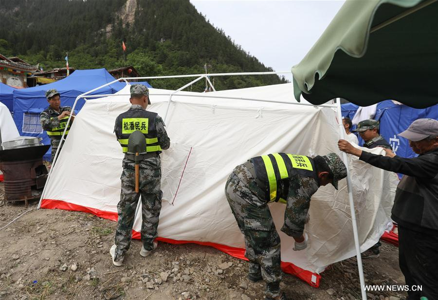 Rescuers set up tents for local Tibetan villagers as temporary settlements in Shuzheng Tibetan Village of quake-hit Jiuzhaigou, southwest China's Sichuan Province, Aug. 10, 2017. Temporary settlements were established in Tibetan villages of Jiuzhaigou after a 7.0-magnitude earthquake struck Jiuzhaigou County on Tuesday. Relief supplies have been provided to aid quake-affected people. (Xinhua/Jiang Hongjing)<br/>
