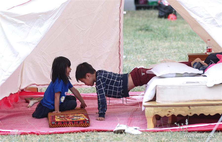 Two kids play at a temporary settlement in Heye Tibetan Village of quake-hit Jiuzhaigou, southwest China's Sichuan Province, Aug. 10, 2017. Temporary settlements were established in Tibetan villages of Jiuzhaigou after a 7.0-magnitude earthquake struck Jiuzhaigou County on Tuesday. Relief supplies have been provided to aid quake-affected people. (Xinhua/Jiang Hongjing)<br/>