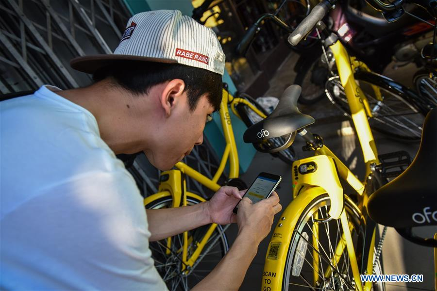 A tourist is about to unlock an ofo sharing-bike at a commercial area in Phuket, Thailand, Oct. 5, 2017. China's dock-less bike-sharing company ofo provided more than 1,000 bikes in Phuket's key locations in late September and offered a 1-month free trial without deposit fee. Now the bike-sharing service has benefited local residents and tourists. Ofo's regular service fee will be charged at 5 Baht per 30 minutes usage, with a deposit fee of 99 Baht. (Xinhua/Li Mangmang)<br/>