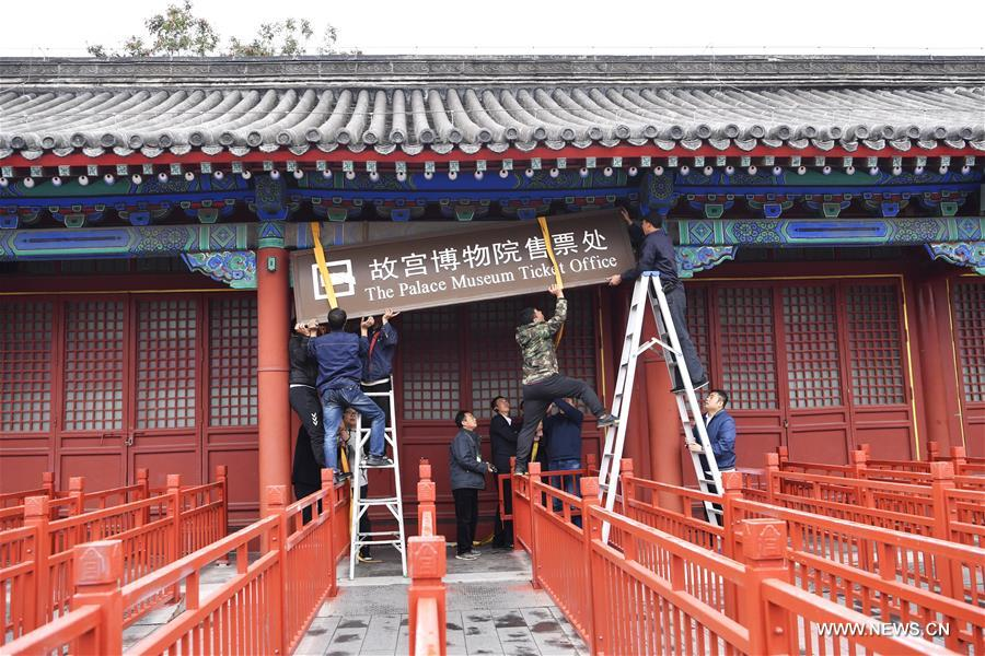 Staff members of the Palace Museum, also known as the Forbidden City, remove the plaque of the ticket office in Beijing, capital of China, Oct. 10, 2017. The Palace Museum has begun to sell all its tickets online only since Oct. 10, 2017, and it will set up a service office to help visitors book tickets online. (Xinhua/Jin Liangkuai)<br/>