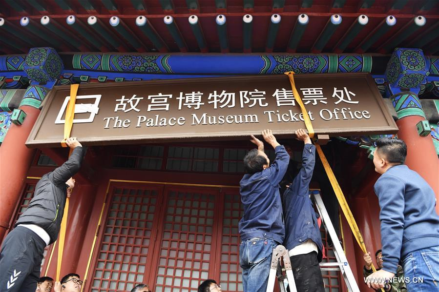 Staff members of the Palace Museum, also known as the Forbidden City, remove the plaque of the ticket office in Beijing, capital of China, Oct. 10, 2017. The Palace Museum has begun to sell all its tickets online only since Oct. 10, 2017, and it will set up a service office to help visitors book tickets online. (Xinhua/Jin Liangkuai)