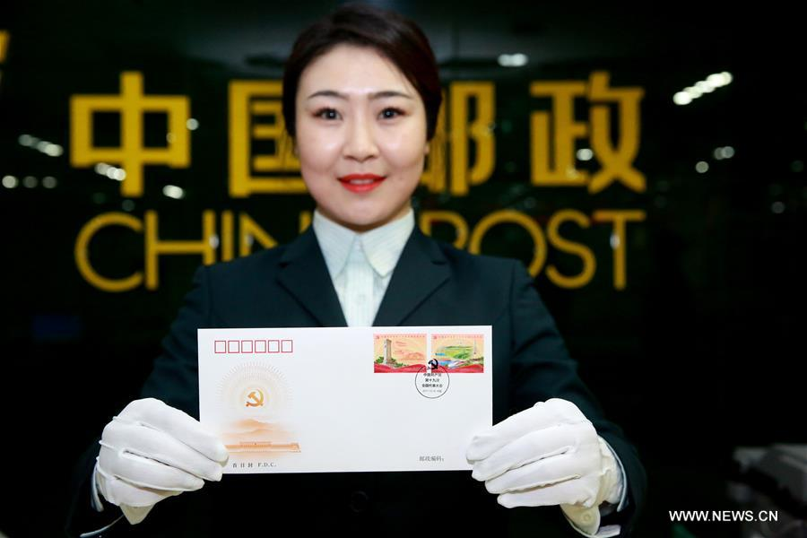 A postal staff member shows a first day cover in Shijiazhuang, north China's Hebei Province, Oct. 18, 2017. China Post issued a set of commemorative stamps marking the 19th National Congress of the Communist Party of China on Wednesday. The set consists of two stamps and a stamp sheetlet. (Xinhua/Zhan Xincheng)<br/>