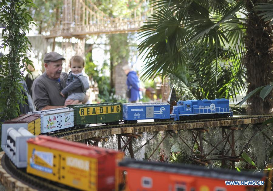 Visitors watch a model train during the Holiday Train Show at New York Botanical Garden in New York, the United States, on Nov. 28, 2017. The Holiday Train Show opens to public from Nov. 22, 2017 to Jan. 15, 2018, displaying around 150 New York landmarks made out of plant parts and large-scale model trains. (Xinhua/Wang Ying)<br/>