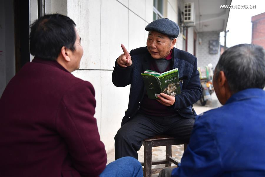 Li Chunru (C) talks about the protection of migratory birds with local residents near Poyang Lake nature reserve, east China's Jiangxi Province, Nov. 28, 2017. Poyang is a seasonal destination for over a million birds every year. Doctor Li Chunru has been voluntarily taken care of migratory birds at Poyang Lake nature reserve for more than 30 years, bringing over 50,000 wounded wild birds out of danger. (Xinhua/Hu Chenhuan)<br/>