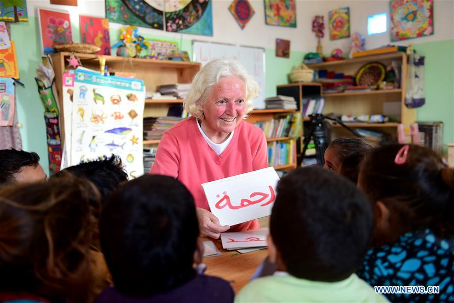 Lady Didi (C) teaches children Arabic at her Nile River School in Ayyat district on the outskirts of Giza Province, about 100 km south of Cairo, capital of Egypt, on March 26, 2017. Diana Sandor, known as Didi, an old Hungarian-born German-raised woman, covered the long distance from West to East six years ago to open her Nile River School as a charitable kindergarten and educational center at the heart of remote, impoverished Baharwa village of Ayyat district on the outskirts of Giza Province, about 100 km south of the Egyptian capital Cairo. Didi said she started building the center 'brick by brick,' through little donations from friends and volunteers around the world and that she is concerned with 'teaching children life,' not just languages and skills. (Xinhua/Zhao Dingzhe)