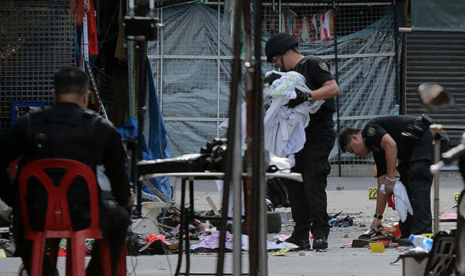 Policemen investigate blast site in Manila, the Philippines