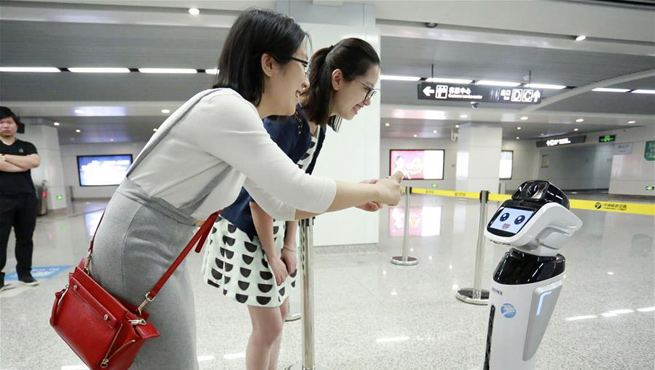 "People interact with intelligent robot ""Xiaogui"" in E China"