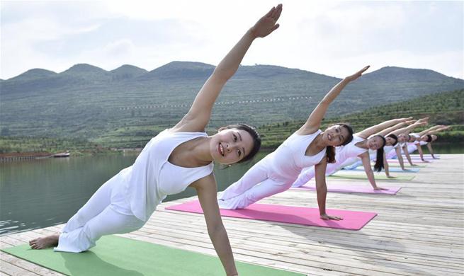 Yoga fans practise yoga across China