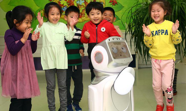 Children play with interactive education robot at kindergarten in N China