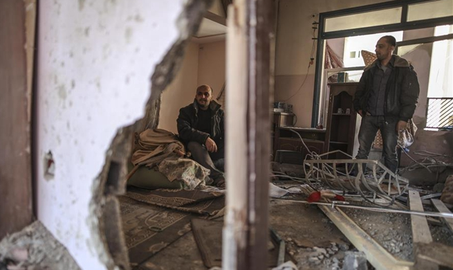 People check damaged house after Israeli airstrikes on Gaza