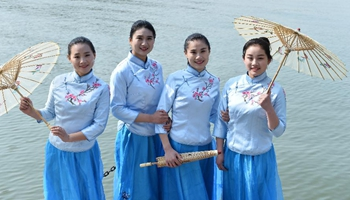 Service staff present workwear at fashion show in E China's ancient town