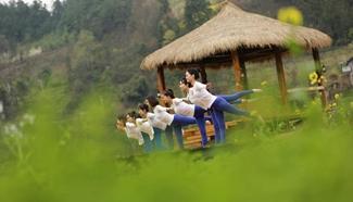 Yoga fans practise yoga on farmland of flowers in C China's Zhangjiajie