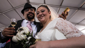 Couple poses after getting married during collective wedding ceremony in Mexico City
