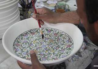 Palestinian workers paint on ceramic article in Hebron