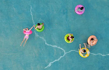 People cool off in swimming pool in east China