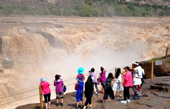 Tourists view Hukou Waterfall of Yellow River