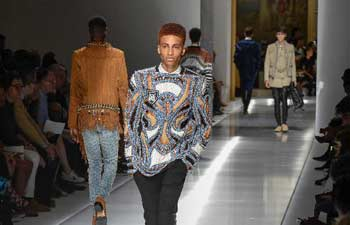 Models present creations of Balmain at Paris Men's Fashion Week