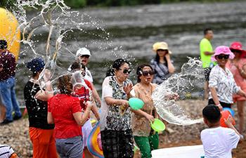 People take part in water-splashing fair along Yichun river of N China