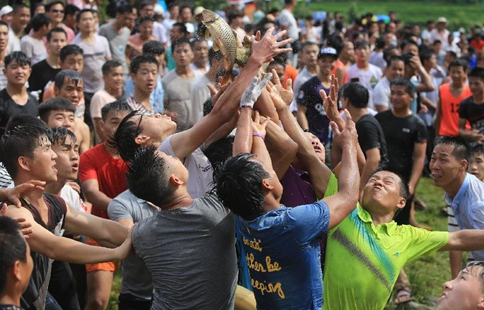 Villagers scramble to catch fish in S China's folk festival
