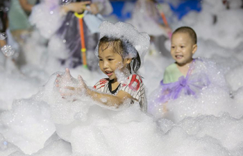 Children play in bubbles during fair in E China's Jiangsu