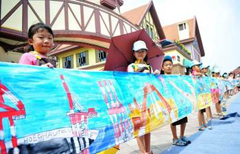 Children paint on scroll to depict hometown in E China