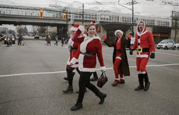 People dressed in Santa Claus' costumes during SantaCon event in Canada