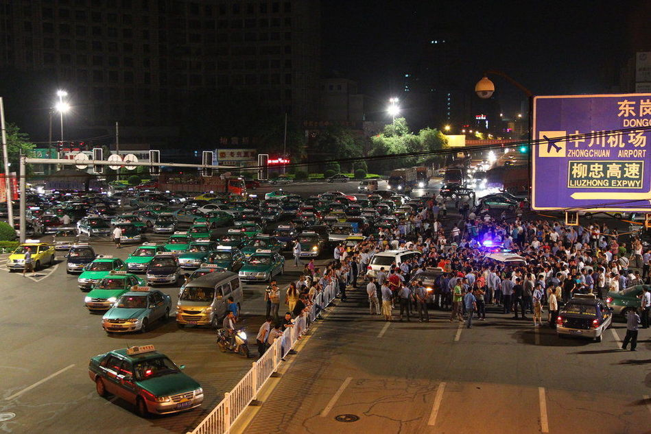 兰州 天水/图为兰州市区街头民众围堵打人司机及其私车,当地警察维护现场...