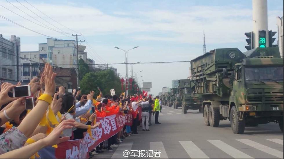 6月9日上午,湖北省监利县,大街两侧,群众挥手向官兵告别。