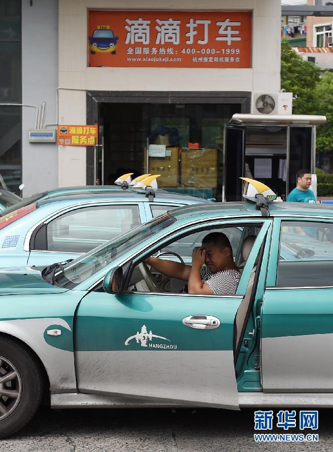 9月16日,一位出租车司机在杭州一处出租车服务区内休整,不远处