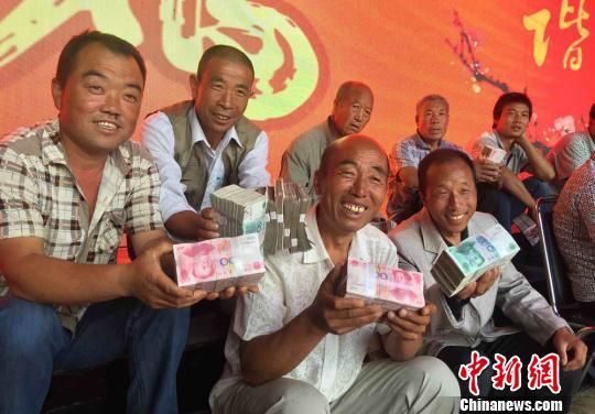图为领到分红的村民开心坐在一起聊天。
