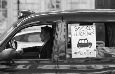 """0日,伦敦黑色出租车司机打出标语,抗议伦敦交通局同意授予""""优"""