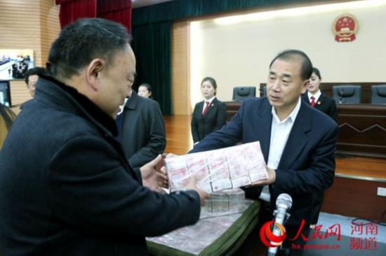 12月5日,河南洛阳市中级法院一号审判庭内,农民工代表拿到执行款3.9亿元。