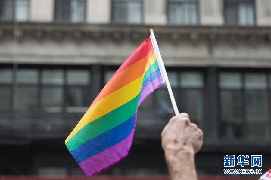 6月28日,在美国纽约曼哈顿,一位民众手持彩虹旗观看同性恋高清图片