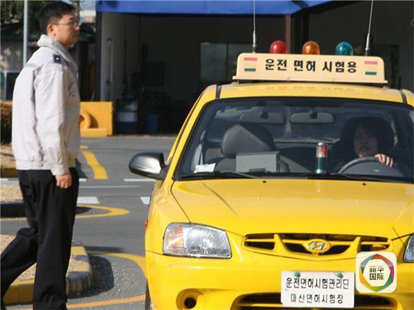 """图为韩国某驾校培训场景,黄色车上写着""""驾照考试用车""""。韩联社发"""