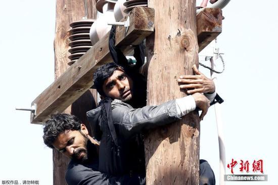 当地时间2016年4月6日,希腊莱斯博斯岛Moira,移民示威抗议被驱逐,两名难民干脆爬上高压电杆,警察随即上前劝阻。