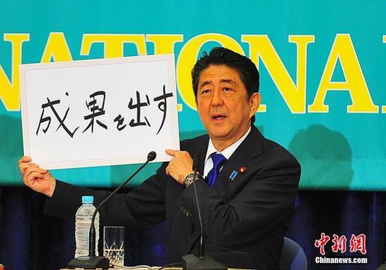 """日本参议院选战在即,6月21日在日本记者俱乐部进行的选前党首辩论会上,""""安倍经济学""""的成败功过再度成为热辩之题。图为安倍现场高调亮出""""搞出成果""""字牌。<a target='_blank' href='http://www.chinanews.com/'><p  align="""