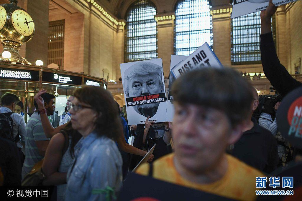 """当地时间2017年9月18日,美国纽约,当地民众在纽约中央火车站集会,举行""""反白人种族主义""""集会,抗议总统特朗普。特朗普将在9月19日联合国大会首日发表演讲。***_***Protesters hold placards with slogans against US President Donald Trump during Rise and Resist Against White Supremacy demonstration inside the Grand Central Station in New York on September 18, 2017. US President Donald Trump will deliver his maiden address on Day One of the 72nd session of United Nations General Assembly on September 19, 2017. Jewel SAMAD"""