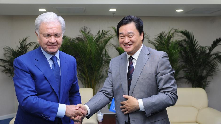 新华网董事长、总裁田舒斌与上海合作组织秘书长阿利莫夫亲切握手