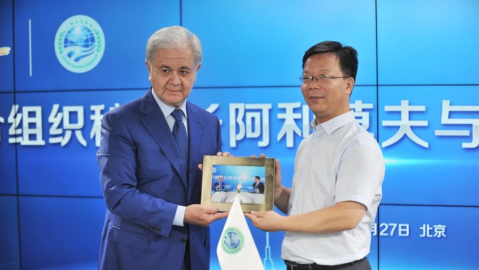 新华网副总编辑刘加文向上海合作组织秘书长阿利莫夫赠送访谈现场照片