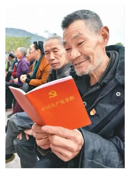 老党员李明友在十九大精神院坝宣讲会上认真学习新《党章》.熊波