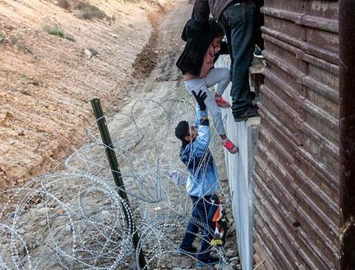 中美洲移民滯留美墨邊境 試圖翻越邊境墻入境