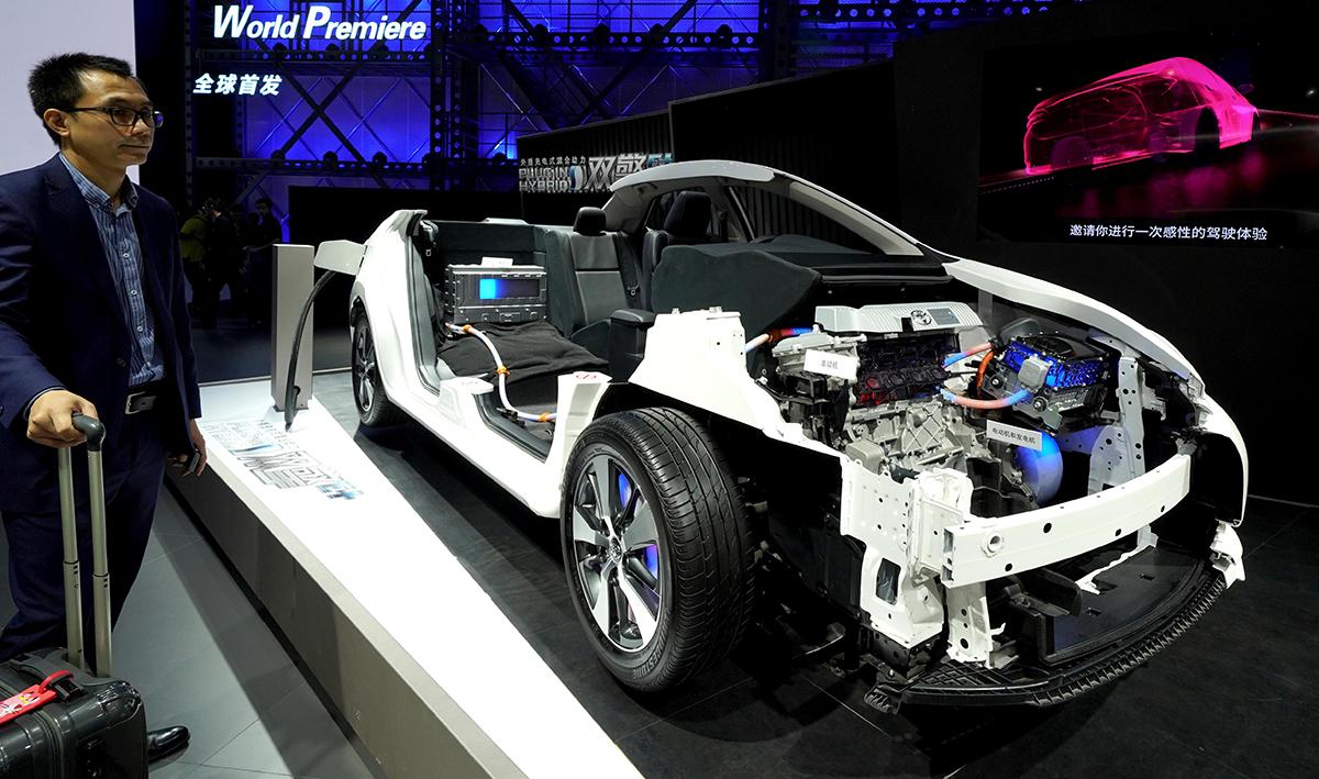 一位觀眾觀看豐田汽車公司展出的外插充電式混合動力工作原理模型